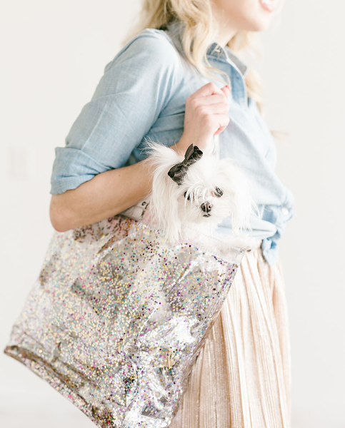 Woman stands holding confetti tote with a white dog inside.