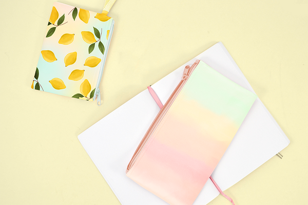 Lemon Sorbet and Daybreak pencil pouches laying on a yellow table with a notebook.