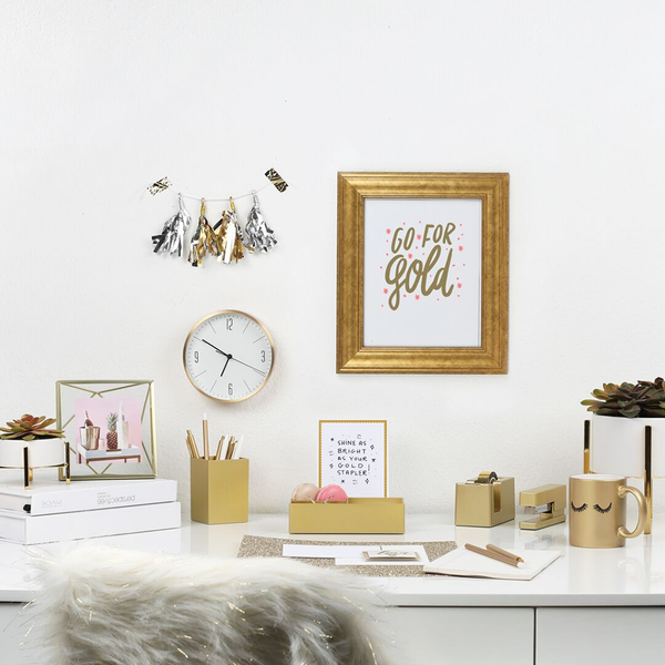 "A office scene with a gold frame on the wall. The frame contained a gold and pint print with the text ""Go For Gold"""