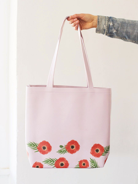 Girl holding a cute tote bag in pink with red poppy pattern.