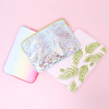 Pile of cute laptop sleeves in Buds, Confetti, and Meltdown sitting on a pink table. Meltdown is pastel rainbow, confetti is clear vinyl and buds is a pink background with green palms all over the bottom half.