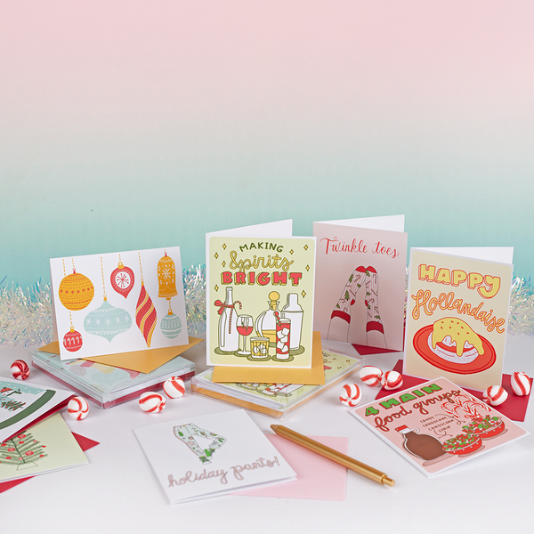 "A group of assorted holiday cards. From left to right on top row: a white card with assorted ornaments, a beverage decorated card with text ""Making spirits bright"", a white card with holiday socks & text ""twinkle toes"", a white, yellow & pink printed card with ""Happy Hollandaise"". On bottom from left to right: a white, light green, medium green & pink card with holiday graphic decorated pants & text ""holiday pants!"", a white, red & green card with syrup & candies with text ""2 main food groups""."
