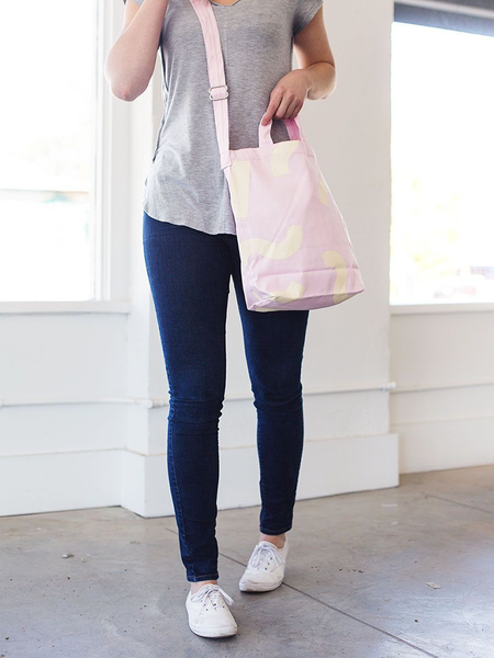 Girl in white sneakers wearing a cute crossbody tote in light pink canvas with macaroni pattern.