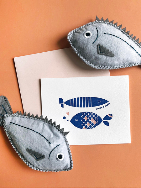 "White greeting card with two blue fish and the text ""you're a catch"". There are gray felt fish above and below the fish"