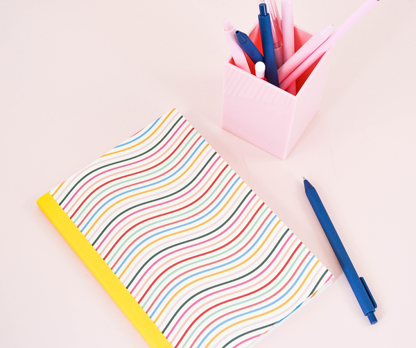 Small notebook with cute and colorful wavy lines across the cover and yellow binding next to a blush pink pen cup with pens