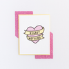 White greeting card with a pink heart and yellow banner, both outlined in black. The banner has the text