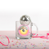 A image of the glass mug with the day dreamers club logo printed on front in yellow and pink colors, and with confetti and small disco balls decorating the mug.
