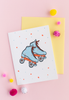 White greeting card with blue and coral/orange skates with dots and stars. There is a yellow envelope and colorful poms in the background.