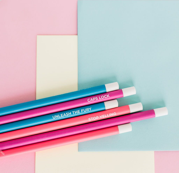 Six pencils in bright blue, pink and neon coral with different phrases printed and laying on colored paper.