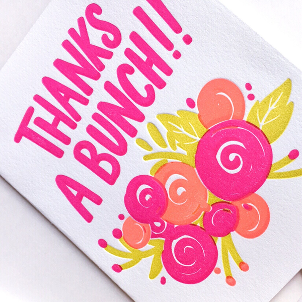 "A white greeting card with the text ""Thanks A Bunch!!"" in bright pink. There are bright pink, orange and yellow flowers and leaves at the bottom. The card is a diagonal and cropped close up photo."