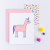 White greeting card with a light pink, dark pink and blue unicorn. There is a light pink envelope, a multi colored polka dot small gift bag and colorful poms.