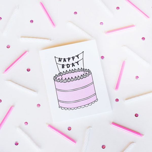 "A white greeting card with a pink, black and white birthday cake. On top of the cake is a banner with the text ""HAPPY BDAY"" in black letters. The background has white and pink candles scattered and pink sequin."