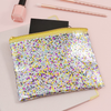Small zippered pouch in clear vinyl with glitter confetti and a gold zipper.