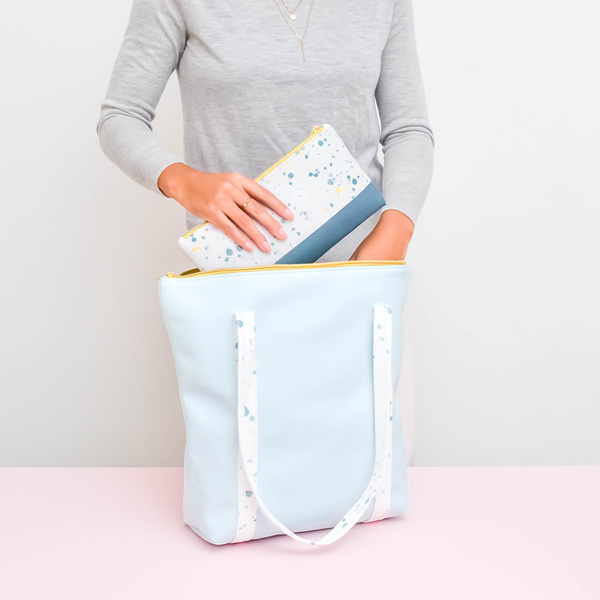 Girl holding a cute tote bag in light blue vegan leather with white paint splatter straps and zippered top.
