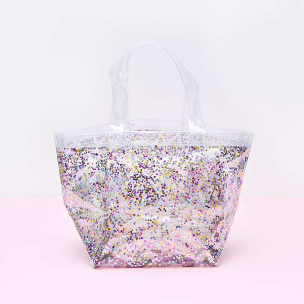 A small confetti tote sits on a pink surface.