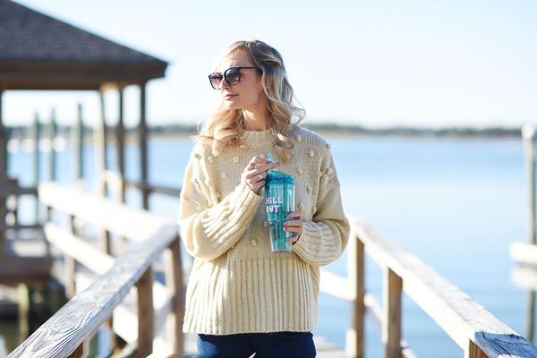 a girl holding Clear plastic drink tumbler in aqua blue with matching straw and 'Chill Out' printed in pink.