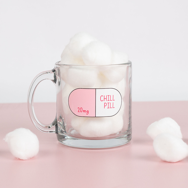 Lifestyle photo of a chill pill glass mug filled with cotton balls on a pink table.