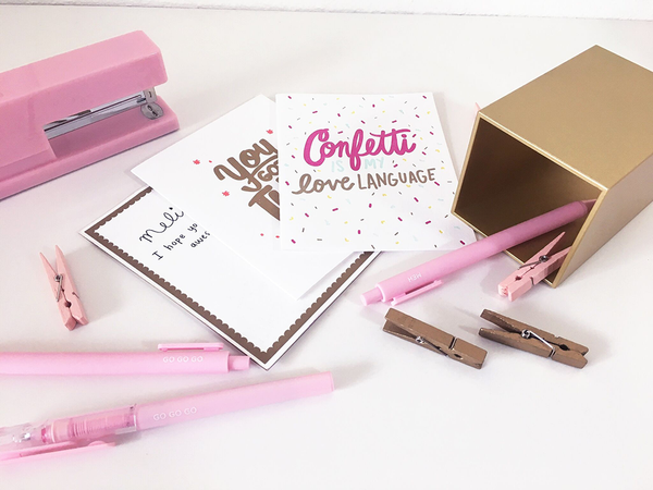 "A collection of white greeting cards surrounded by pink and gold desk set items. The card on top has the text ""Confetti is my love language"" in pink, light blue and gold. The text is surrounded by multi colored confetti."