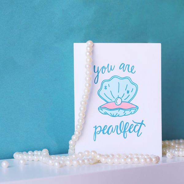 "A white greeting card with a blue and pink clam opened to show a pearl. The blue script text above the clam is ""you are"" and below the clam is ""pearlfect"". The card is standing open with pearls hanging on it and a blue wall in the background."