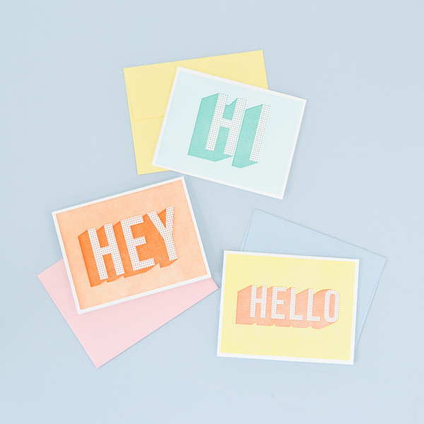 "Image of three greeting cards. The top one is light green with a dot pattern that says ""HI"". The middle one is orange with a dot pattern that says ""HELLO"". The bottom one is yellow with a dot pattern that says ""HELLO""."