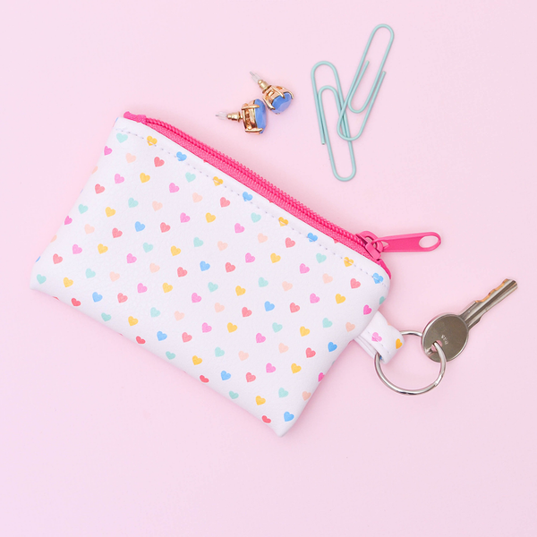 A cute coin purse key ring in blush pink with rainbow hearts pattern and a coral zipper.