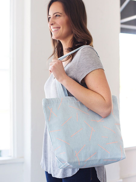 Smiling brunette girl holding a light blue canvas tote bag.