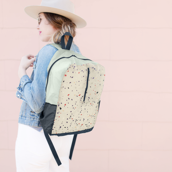 a ripstop backpack with terrazzo print over a girls shoulder