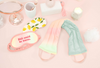 a pastel neck wrap, lemons weighted eye mask, and a pastel sleep mask on a pink background
