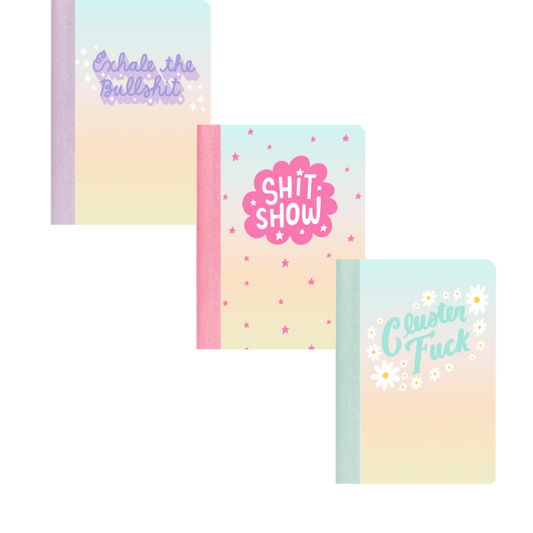 "A plain background with 3 mini notebooks. One that says ""exhale the bullshit"" in purple, one says ""shit show"" in pink and ""cluster fuck"" in blue."