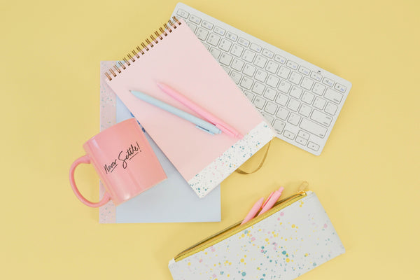 Pink taskpad with a metallic gold elastic closure and small white section of paint splatter at the bottom laying on top of a white keyboard with a pink mug and pink jotters