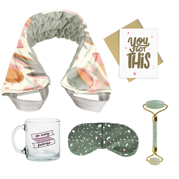flat image of a collection of self care items including a neck wrap with a muted abstract floral print, a clear glass mug that says so many feelings, a weighted eye mask with green terrazzo imprint, a greeting card that says you got this, and a jade roller with roll with it imprinted in dark green.