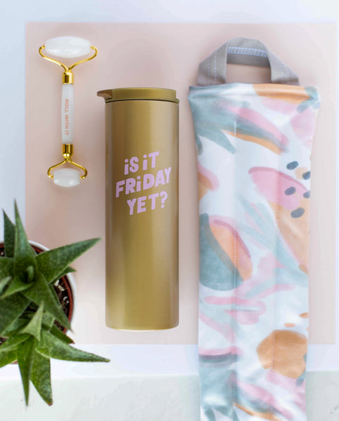 A weighted neck wrap with mutey fruity print laying next to a gold steel tumbler that says is it friday yet, and a white stone roller
