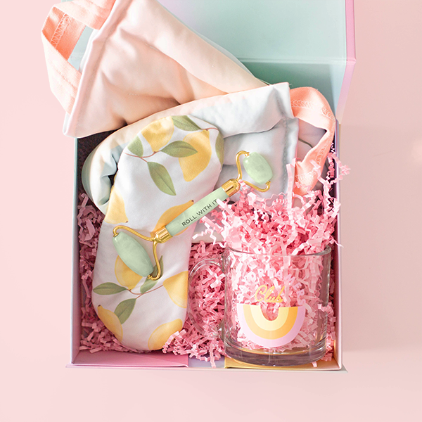 A gift set containing a clear glass mug with Daydreamers Club written in blue, a neck wrap with a soft rainbow gradient print, a lemon printed eye mask, and a jade face roller all in pink crinkle paper and packaged in a colorful box.