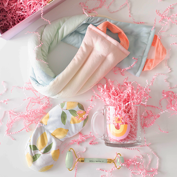 Contents of a gift set laid out to show a neck wrap with a pastel ombre print, a weighted eye mask with lemons printed on it, and a jade face roller amidst pink paper shreds.