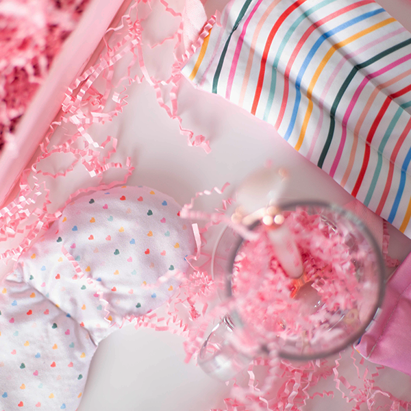 Contents of a gift set laid out to show a neck wrap with wavy rainbow lines, a weighted eye mask with tiny hearts printed on it, and a rose quarts face roller in a clear glass mug amidst pink paper shreds.