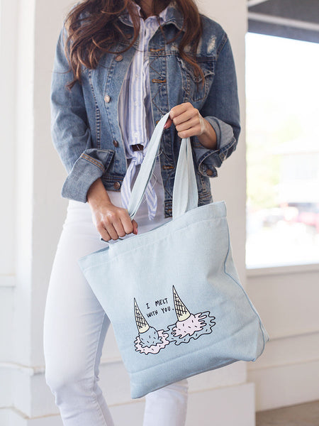 Brunette girl in denim jacket holding a denim tote bag with i melt with you double ice cream cones print.