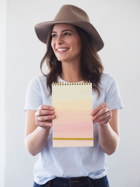 A happily smiling young woman holding a taskpad with a soft rainbow gradient in front of her.