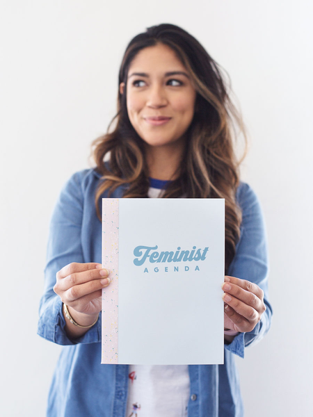 Cute young woman holding a small light blue notebook in front of her that says Feminist Agenda.