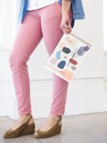 A woman in pink pants holding a large taskpad in one hand with an abstract art print on the cover.