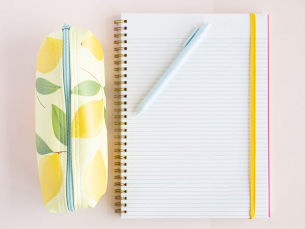 a lemons jitterbug next to a notebook and a jotter