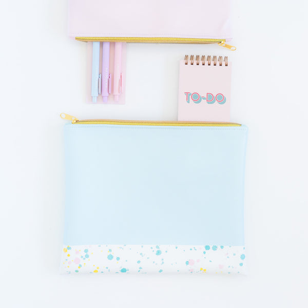 Small pink taskpad with a metallic gold elastic closure and To Do written on the cover inisde a blue splatter pouch