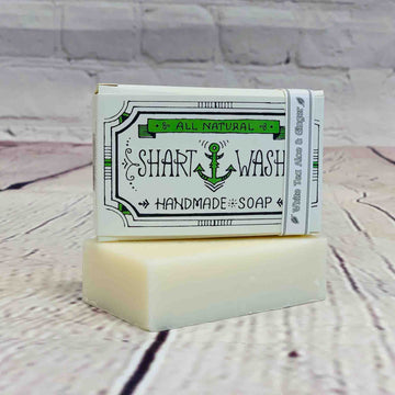Picture of a box of Shart Wash Natural Handmade Bar Soap White Tea Aloe and Ginger scent sitting on a White bar of soap with a wood background