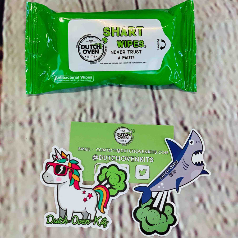 Picture of 1 pack of Shart Wipes antibacterial hand and surface wipes on a wood background with a business card, farting unicorn sticker and a farting shark sticker