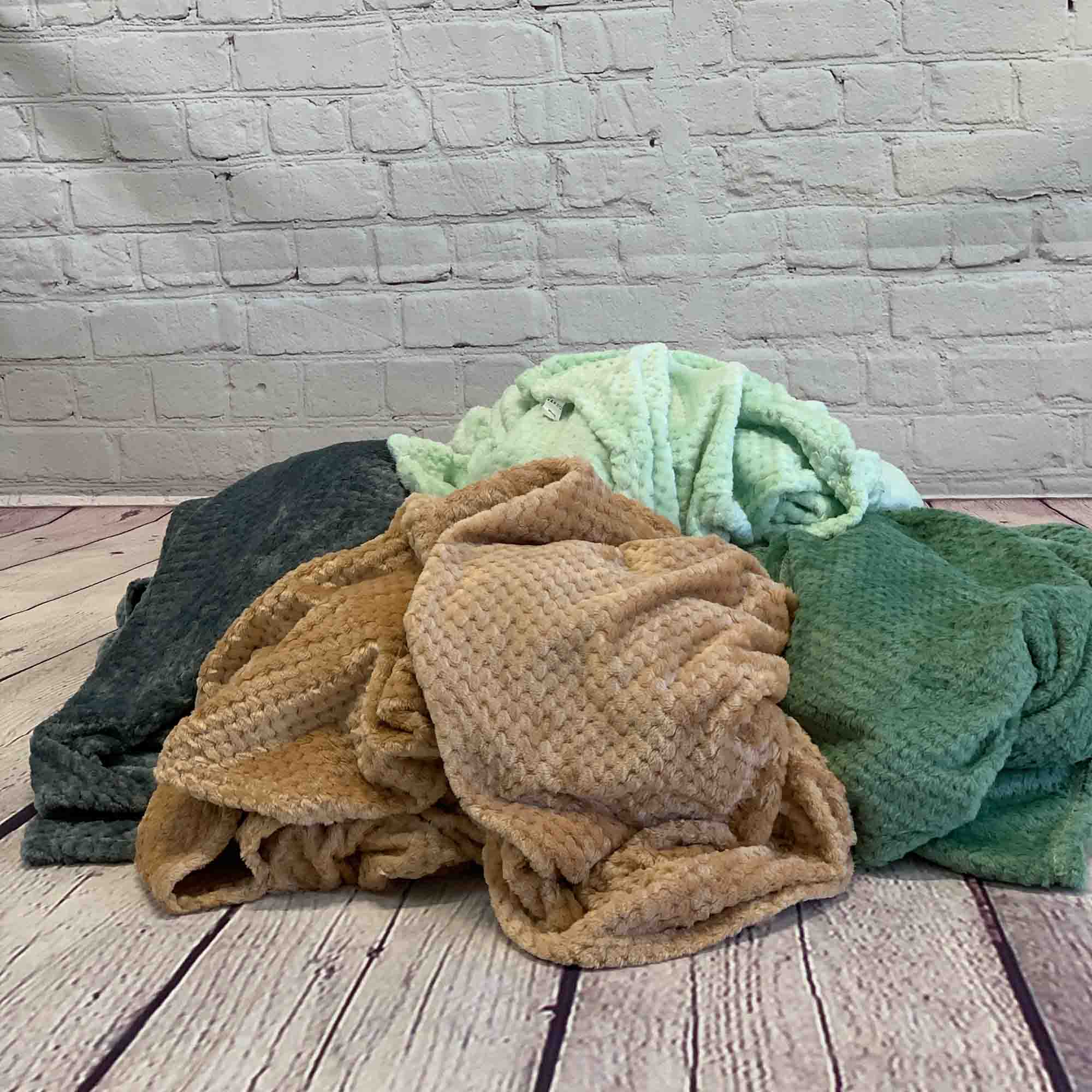 Image of a group of Microfiber fleece throw blanket on a wood plank floor
