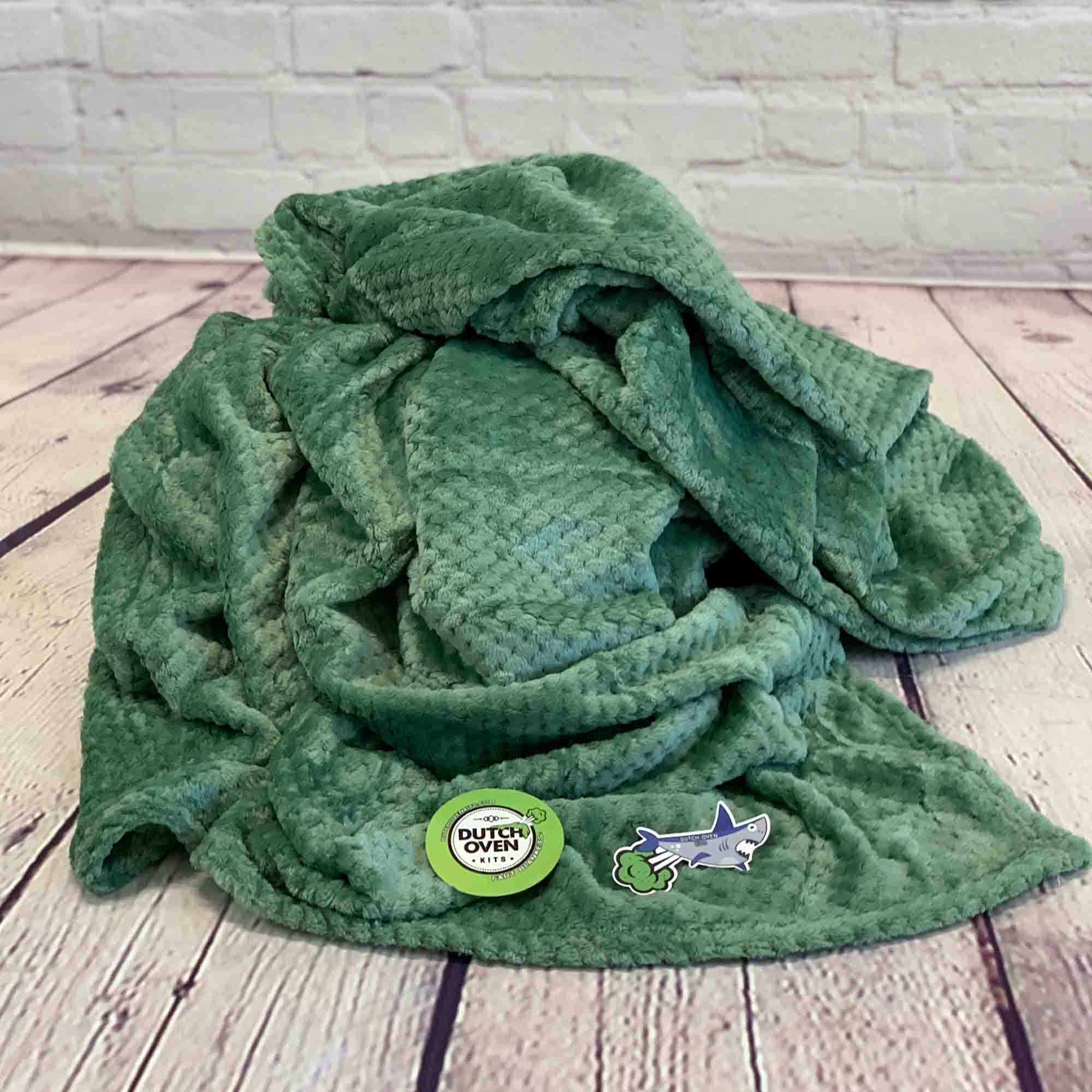 Image of a Dark Green color Microfiber fleece throw blanket on a wood plank floor
