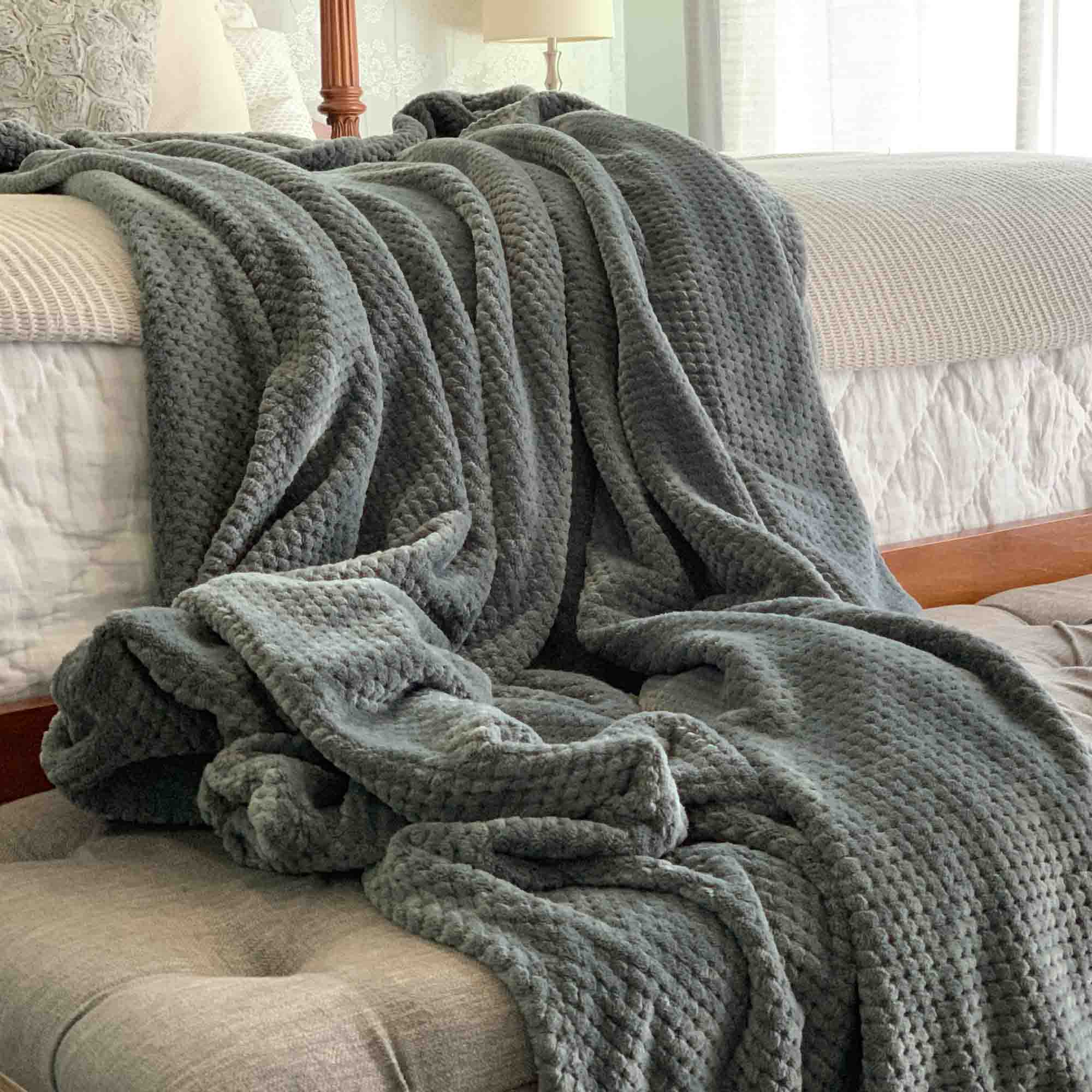Image of a gray color Microfiber fleece throw blanket draped over a bed and bench