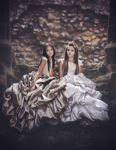 two girls wearing ball gowns at a castle