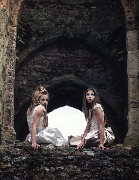 two girls sitting on a castle ledge