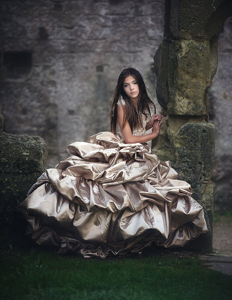 girl wearing a big beautiful champagne gown in front of a castle