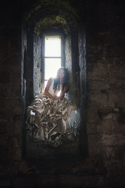 a girl wearing a golden dress sitting in a stone castle window